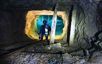 Tunnel leading deep into a copper mine. Insets from top: Diver looking down a flooded inclined railway shaft; exploring deeper into a mine.